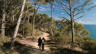 Couple of tourists or travellers walk on romantic getaway adventure path in middle of national park on seaside or ocean, explore world destinations together