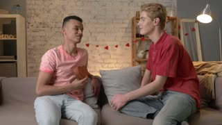 Couple of young multinational gay men sit on the couch, an African American presents a a casket in the shape of a heart. LGBT concept.