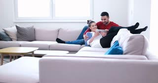 Couple Relaxing On Sofa Using Digital Tablet In Living Room