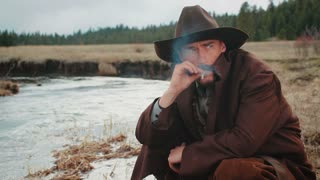 Cowboy Sitting By River Smoking
