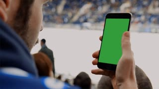 CU Caucasian male using his phone during hockey game intermission in large sports venue. Green screen chroma key on the phone. 4K UHD RAW edited footage