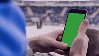 CU Caucasian male using his smart watch during hockey game intermission in large sports venue. Green chroma key on the watch screen. 4K UHD RAW edited footage