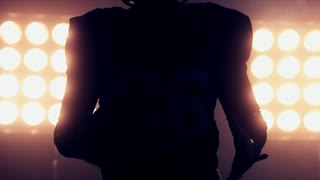 CU Silhouette of male American football player holding a ball in his hands against bright stadium illumination lights. 4K UHD RAW edited footage