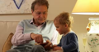 Cute Candid Moment Of Grand Father And Grand Son Together On Living Room Sofa Grand Father And Infant Grand Son Eating Peanuts Together In 4K