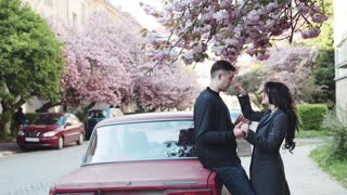 Cute couple having a conversation in the city by the red car, she squeezes the nose of her boyfriend, he throws cherry blossom petals, they are laughing happily. Love story, having fun, true emotions