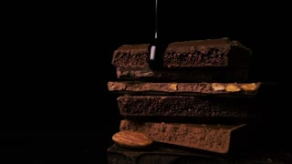 Dark hot chocolate pours a thin trickle down onto the fragments of chocolate on a black background. Slow motion