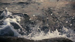 Dark water creates a wave crashing against rocks with foam and bubbles and ebb slow motion