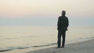 Disappointed mature businessman standing by the sea shore. Old man in suit having negative changes in his business career and facing bankruptcy. Gloomy mood.