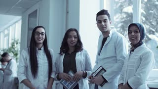 Diverse group of four young medical students stood together