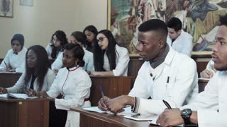 Diverse mixes ethnic medical students in hospital lecture theater taking notes