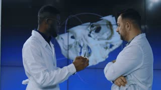 Diverse professional scientists in medical robes having 3-D printed model of human cranium exploring its peculiarities. Movement stabilized 4K shot.