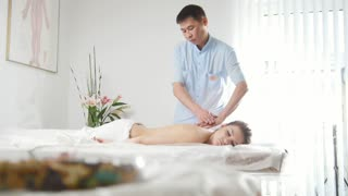 Doctor massagist and patient - young woman lying on massage table - spa procedure