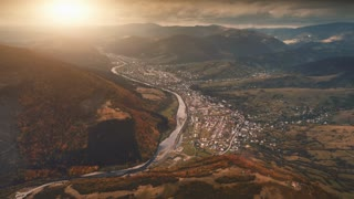 Dramatic Drone Flight over autumn village in mountain canyon. Farm meadows, orange hills, pine tree forests and river against sunset sky. Carpathians, Ukraine, Europe. Vintage retro toning filter. 4K