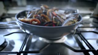 Dramatic zoom into wok pan on top of metal steel gas stove full of steaming vaporized mussels. Delicious mouth watering seafood cuisine in restaurant, freshly made to order