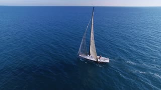 Drone flies around beautiful solo white yacht or sailboat lost in wide vastness of open blue sea or ocean, on weekend day out on summer luxurious vip holiday, expensive hobby