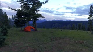 Drone flying by a tent in the Colorado Rocky Mountains at sunset