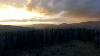 Drone flying over the woods in nature towards a sunset with golden clouds