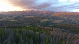 Drone flying slowly backwards to reveal a colorful sunset in the Colorado Rocky Mountains