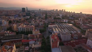 Drone footage changes view from following city skyline to top view of traffic street crossing with vehicles, cars, busses and motorbikes riding through green light in early morning