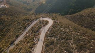 Drone footage over lonely traveler riding his motorbike on epic scenery mountain roads, turning in big loop on serpentine, camera tilts down to top view at sunny day
