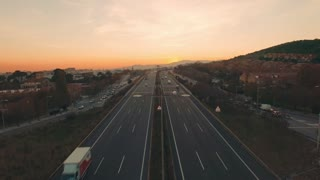 Drone is flying slowly toward sunset sun above big six lane two directional highway road busy with traffic and fast moving cars, motorcycles and trucks, in center, very close to street lights