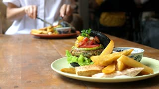 Eating Broccoli Burger With Fries In Healthy Vegan Cafe