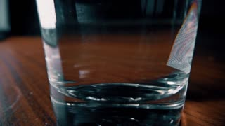 Effervescent tablet falling into glass of water. 4K close-up slow motion shot