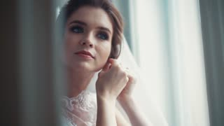 Elegant blue-eyed bride in a beautiful white wedding dress and bridal veil puts on earrings. Wedding preparation, happiness, positive mood