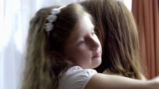 Emotional little girl hugging her loving mother at home