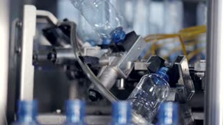 Empty water bottles grabbed from a conveyor line by a cleaning rotary wheel. 4K.