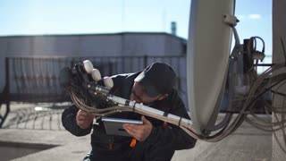 Engineer or technician checking or installing a parabolic dish television antennae and booster on the roof of an urban high-rise using digital tablet