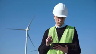 Engineer with seriously face working with digital tablet against wind turbine on sunny day and looking at camera