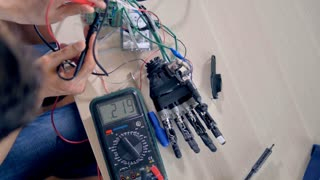 Engineer working with a bionic hand and a multimeter.