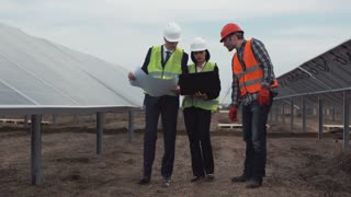 Engineers and the worker in a uniform and hard hat go between rows of photovoltaic panels and talk about construction of power plant solar farm. They look at blueprints