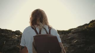 Epic amazing shot of camera following adventure hike walk of young traveler tourist exploring mountain top. Young blonde woman with backpack walks up trail on sunset, reaches summit