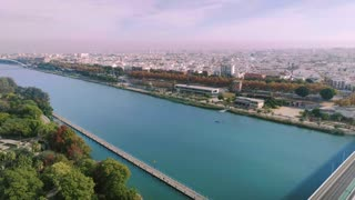 Epic and beautiful aerial drone shot over urban and futuristic city of nearby future, nature and technology mix for better city planning. Big wide water canal of river in seville, spain