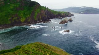 Epic drone footage of amazing beautiful mesmerizing astonishing sea shore with cliffs and rocks in high tide, brutal powerful waves crashing, northern wind blows over green forests