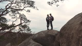 European couple on the top of the rock taking several selfies in a strong wind. Romantic atmosphere. Happy memories, extreme hiking. Splendid nature on the background.