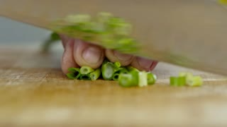 Extreme close up of male hands of professional cook holding knife and chopping fresh spring onion on wooden board