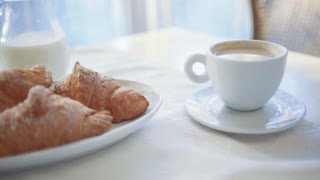 Extreme close up view of morning breakfast, lunch. Rotation view of served cup of coffee with milk, crispy croissants and milk. Perfect morning, daily routine. Cozy atmosphere.