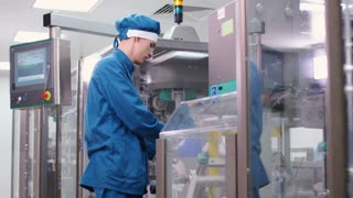 Factory engineer working on manufacturing equipment. Factory worker control production process at pharmaceutical plant. Male employee checking pharmaceutical machine. Pharmaceutical industry