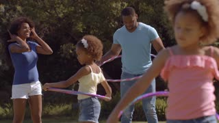 Family playing with hoola hoops in park