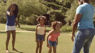 Family skipping with rope in park
