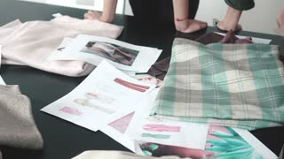 Fashion designers choose fabrics for a new collection of clothes. a group of designers works in a small atelier