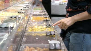 Female Customer Hand Trying Dried Fruits In Supermarket