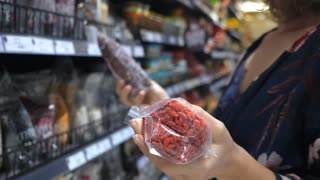 Female Customer Shopping For Superfoods Choosing Goji Berries In Supermarket