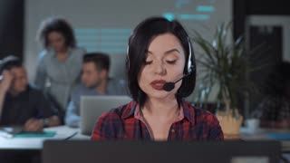 Female operator in call center looking at camera and talking to a customer