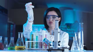 Female scientist using dropper and test tubes for conducting experiment
