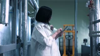 Female scientist walking through lab and checking production equipment while wearing white uniform and holding a tablet