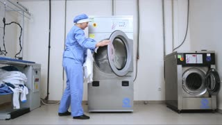 Female worker loading washing machine at hotel laundry. Woman working at industrial laundry service. Employee loading laundry in industrial washer. Commercial laundry room.
